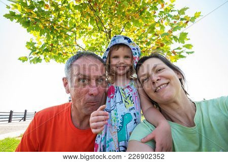 Funny Parents With Small Laughing Daughter Taking Selfie In The Park Against The Background Of A Gre