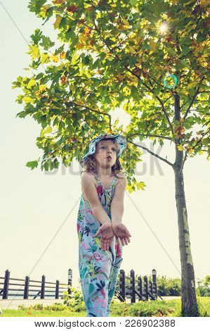 Funny Small Girl Catches Soap Bubbles And Having Fun In Park Against The Background Of A Green Tree,