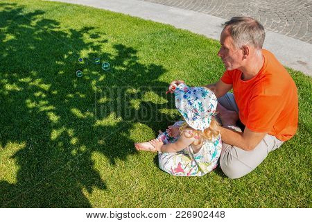 Father With A Small Daughter Relax On A Green Meadow Near The River On A Beautiful Sunny Day, They B