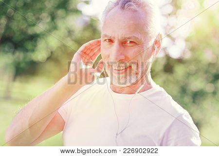 Join Me. Close Up Of Cheerful Man Using Earphones And Listening To The Music While Standing In Front