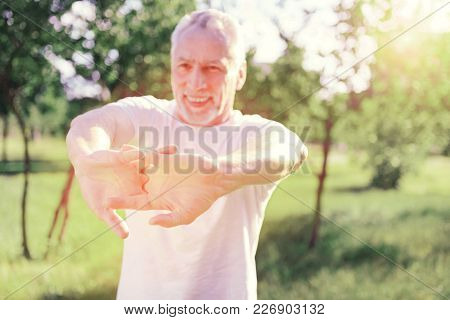 Diligent Sportsman. Close Up Of Enthusiastic Man Keeping Hands Forward While Expressing Cheer And In