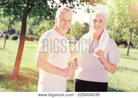 Time Together. Waist Up Of Optimistic Couple Standing Close To Each Other While Looking At You With