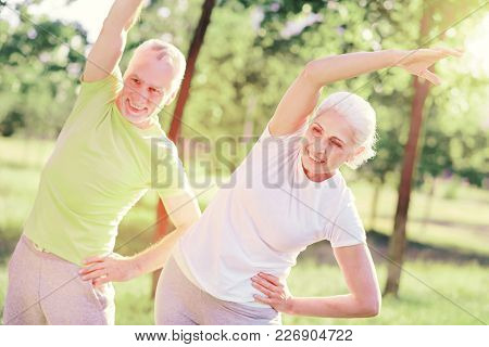 Older And Healthier. Waist Up Of Positive Friends Looking Away While Doing Useful Exercises Outdoors