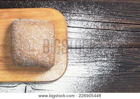 Loaf Of Ciabatta Bread On A Cutting Board On The Dark Wooden Table, Top View With Space For Text