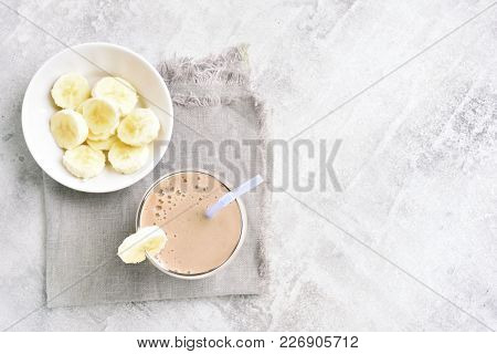Banana Milkshake In Glass On Stone Background With Copy Space. Healthy Beverage. Vegetarian, Vegan D
