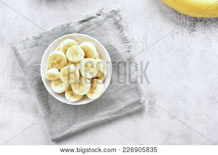 Healthy Natural Food. Sliced Ripe Banana In Bowl On Stone Background With Copy Space. Vegetarian Veg