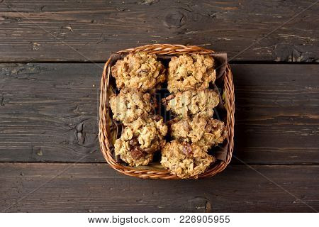 Tasty Oats Cookies In Bread Basket Over Wooden Background. Top View, Flat Lay