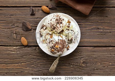 Summer Dessert. Scoops Of Vanilla Chocolate Ice Cream With Nuts In Bowl On Wooden Table. Top View, F