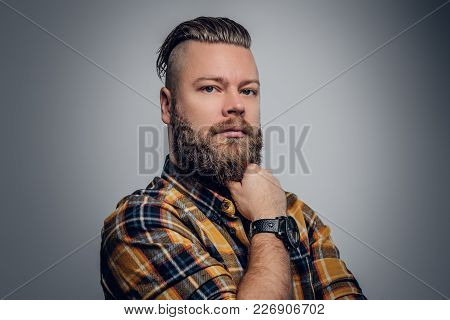 Portrait Of A Bearded Hipster Male With Punk Hairstyle Dressed In A Yellow Shirt On Grey Background.