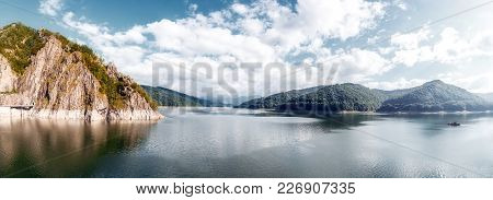 Panorama Of Mountain Lake With Overcast Sky. Of Vidraru Lake And Dam. Hills Glowing In Sunlight. Cre