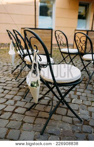 Decorated Outdoor Wedding Ceremony With White Wrought-iron Chairs And Rose Petals In Paper Packets