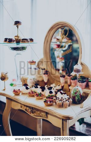 Wedding Desserts Of Caps And Cakes On The Background Of A Mirror In A Golden Color At The Restaurant
