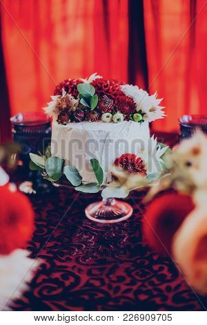 Wedding Cake On The Background Of Decor In A Burgundy Color In The Restaurant With Flowers