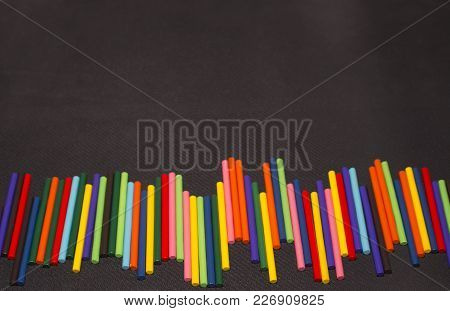 Multicolored Sticks Lay On A Black Background