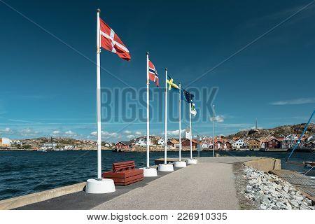 Flags Of Scandinavian Countries Waving On Flagpoles On The Shore. Scandinavian Coastal City.