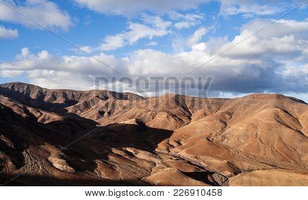 Arid Mountain Scenery On Fuerteventura Against Beautiful Sky