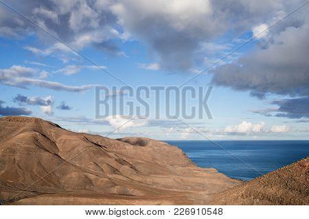 Arid Coastal Scenery Against Beautiful Sky And Blue Ocean