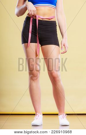 Weight Loss, Slim Body, Healthy Lifestyle Concept. Fit Fitness Woman In Sportswear Measuring Her Bel