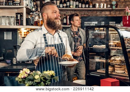 The Stylish Bearded Male Holds Chocolate Cake At The Counter In The Bakery Shop.