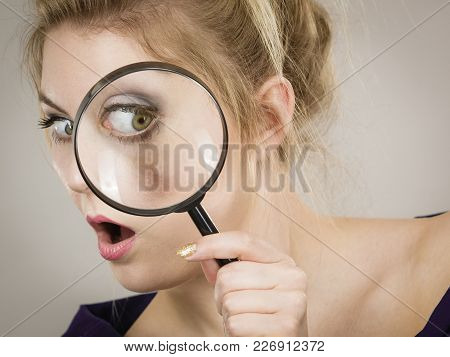 Blonde Woman Holding Magnifying Glass Investigating Something And Looking Closely, Trying To Find So