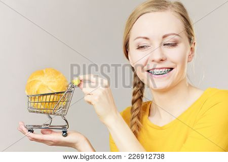 Buying Gluten Food Products Concept. Woman Holding Shopping Cart Trolley With Small Piece Of Bread B