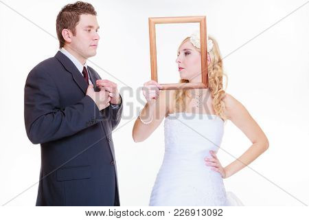 Wedding Day, Negative Relationship Concept. Groom And Bride Holding, Posing With Empty Photo Frame H