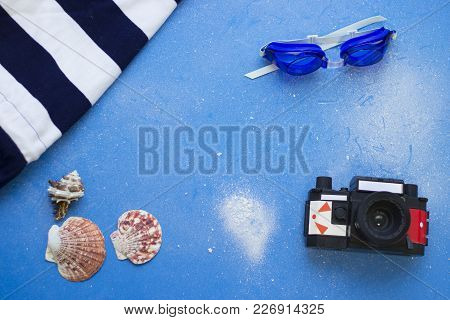 Sea Discovering. Blue One-color Background With Swimming Glasses, Vintage Camera And Beach Clothing,