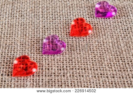 Transparent Figures Of Hearts Are Laid Out On Burlap On Diagonal. Four Multi-colored Figures. Horizo