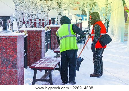 Men In Work Clothes With A Shovel And A Broom To Remove Snow From The Bench And Walkways In The Park