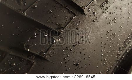 Black Rubber Car Tire Covered With Water Drops At An Angle