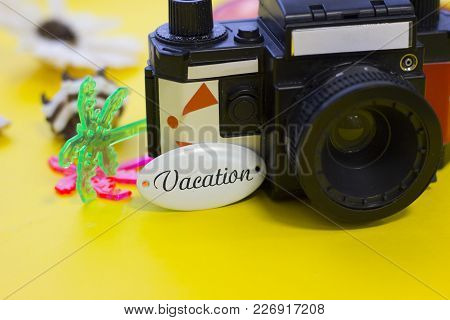 Tourist's Vintage Photo Camera On Yellow Background