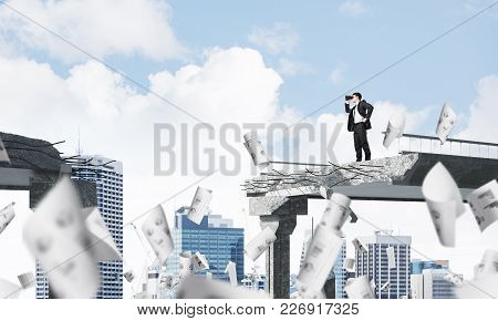 Businessman In Suit Looking In Binoculars While Standing Among Flying Papers On Broken Bridge With C