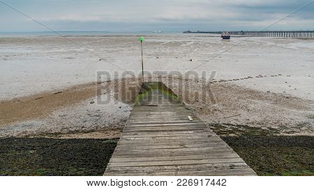 Shoreline Of The River Thames At Low Tide With A Boat And Southend Pier In The Background, Southend-