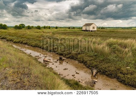 House On Stilts And Some Pylons In The Mud Of The Marshland Near The River Crouch, Wallasea Island,