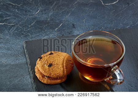 A Transparent Glass Cup Of Black Tea With Cookies On A Dark Greyish Marble Background. Breakfast Bac