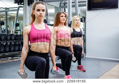 Fitness, Sport, Friendship And Healthy Lifestyle Concept - Group Of Attractive Young Women Doing Lun