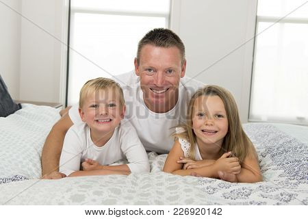 Young Caucasian Man  Lying On Bed Together With Her Little Sweet 3 And 7 Years Old Son And Daughter
