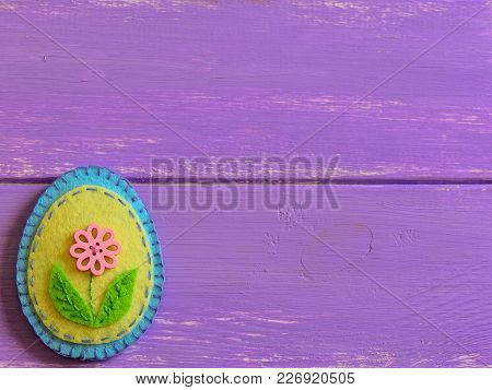 Felt Easter Egg Decor With Pink Flower Isolated On A Wooden Background With Copy Space. Fun Easter C
