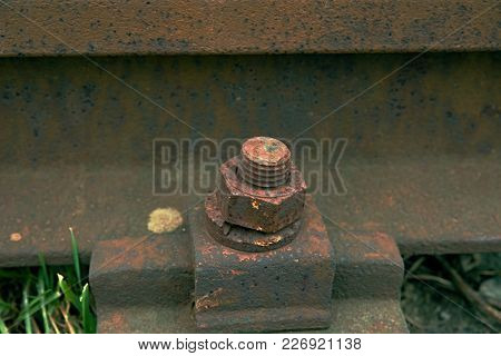 Gap With Nut And Screw On The Old Rusty Rail.  Rusty Train Railway Detail, Oiled Sleepers And Stones