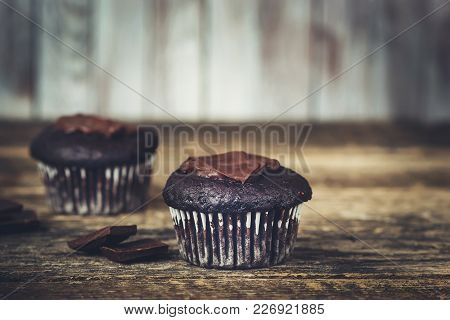 Chocolate Capcakes With Chunks Of Chocolate On The Rustic Wooden Background