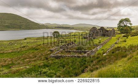 Grey Clouds Over Llyn Cwmystradllyn With A Derelict Ruin On The Shore, Near Penmorfa, Gwynedd, Wales