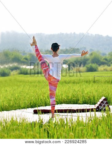 A Woman Do Variation Of Utthita Hasta Padangusthasana Yoga Pose On A Wood Terrace In A Green Rice Fi
