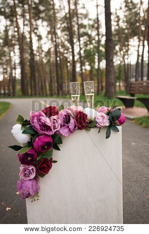 Two Glasses With Champagne Stand On A Pedestal Decorated With Flowers. Wedding Details