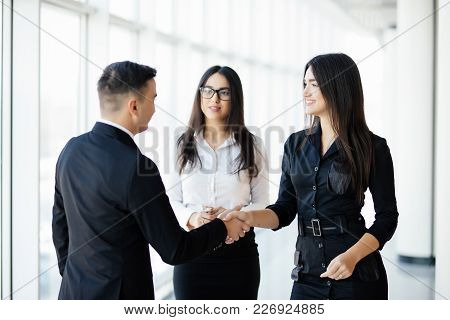 Businessman And Businesswoman Shaking Hands In Bright Office