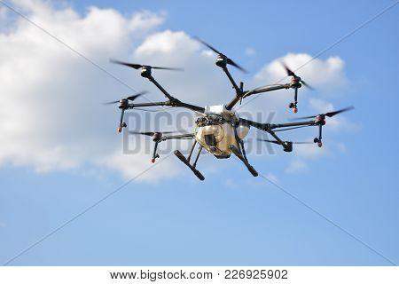 Flying Agriculture Drone, Photo Image Of Agriculture Drone Carry A Tank Of Liquid Fertilizer Flying