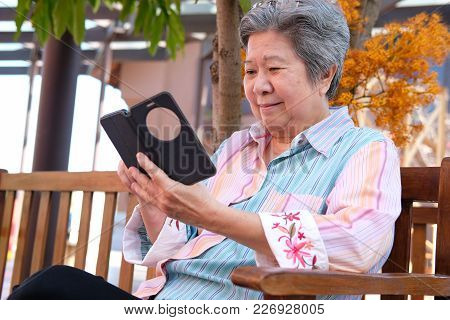 Asian Elder Woman Holding Mobile Phone In Garden. Elderly Female Texting Message, Using App With Sma