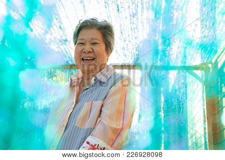 Elder Woman Smiling At Camera. Happy Elderly Female Relaxing Outdoors. Mature Lifestyle Concept