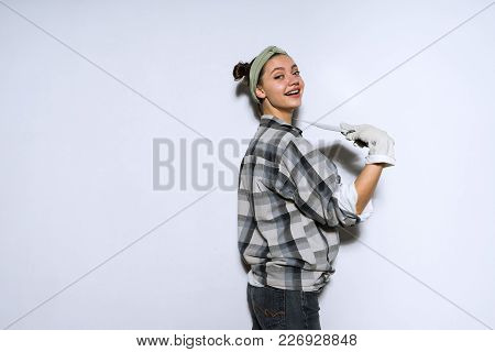 Happy Young Girl Doing Repairs In Her Apartment, Wearing Rubber Gloves, Holding A Spatula