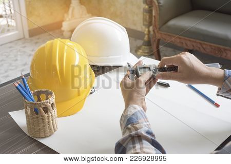 Construction Engineer Measuring With Vernier Caliper. Business And Technology Concept. Safety Helmet