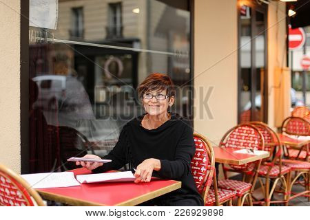 Business Woman Sitting At Table In Street Cafe, Fill Declaration With Tablet And Sheets Of Paper. La